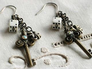 Unique pierced earrings of a key and the dice