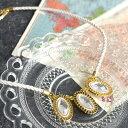 3つの大粒クリアビジューが首元を飾る。ゴールドの縁取りが華やかさをプラスしたデザイン。