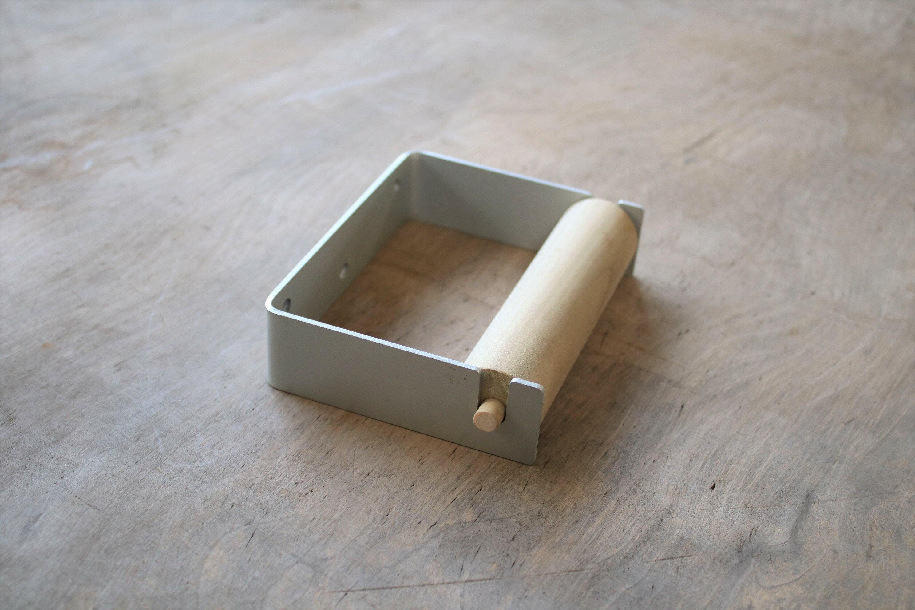シンプルなデザインの中にも温かみのある「つむぎ商會」オリジナルのトイレットペーパーホルダー。本体はシルバーかホワイトのスチール製で、芯は天然木製。金属のクールさとウッディな温かさのコントラストが絶妙です。