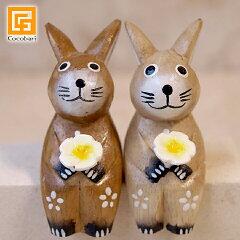 木彫りのウサギS カップル(ナチュラル)。手にプルメリアのお花を持っている愛らしいウサギたち...