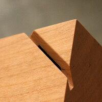 無垢の木材から削り出してつくった貯金箱。